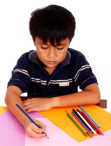 Boy With His Colored Pencils Drawing A Picture