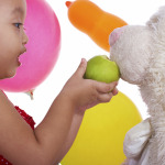 Kid Feeding Her Teddy An Apple